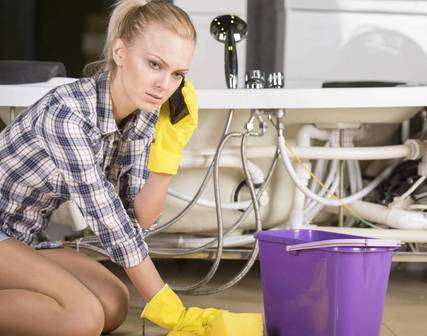 woman cleaning up water calling plumber